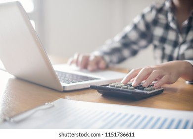 Business woman using a calculator to calculate the numbers