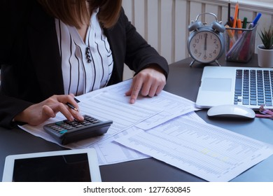 Business woman using a calculator to calculate the numbers on his desk in a office.
