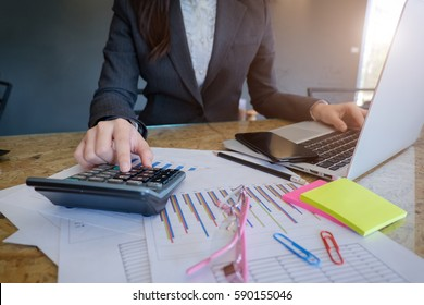 Business woman using a calculator to calculate the numbers on his desk in a office.business concept