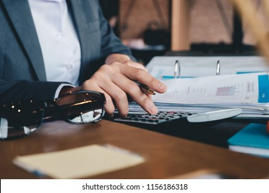 Business woman using calculator and laptop for do math finance on wooden desk in office and business working background, tax, accounting, statistics and analytic research concept