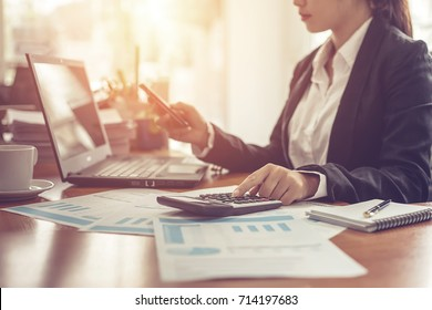 Business woman using calculator and writing make note with calculate. Woman working at office with laptop and documents on his desk