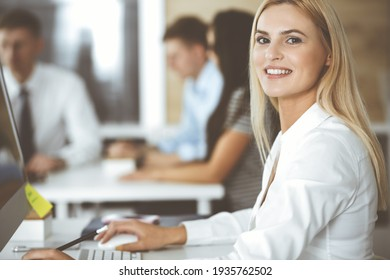 Business woman using computer at workplace in modern office. Secretary or female lawyer smiling and looks happy. Working for pleasure and success