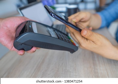 Business woman using her mobile to made a payment wireless with EDC machine. Mobile payment concept.