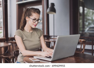 Business woman using laptop at cafe. Young beautiful girl sitting in a coffee shop and working on computer