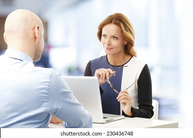 Business woman using laptop and giving advise to her client.