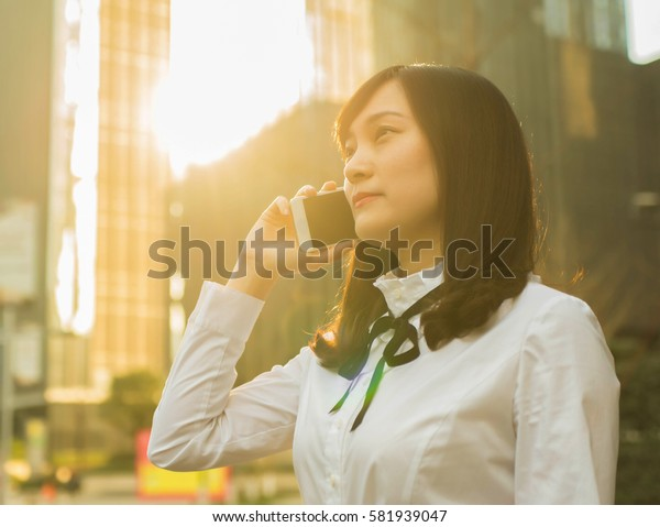 business woman using mobile phone during sunset in front of modern building