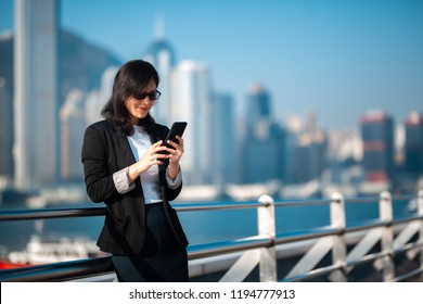 Business woman using the smartphone on waterfront in Hong Kong