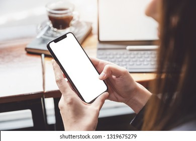 Business woman using smartphone with tablet in caffee shop. smart phone or mobile with blank screen and can be add your texts or others, tecnology concept.