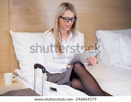 Business woman using tablet computer in hotel room