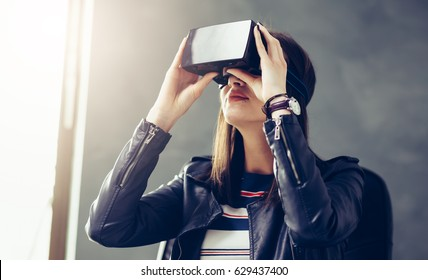 Business woman using virtual reality 3-D glasses headset at the office