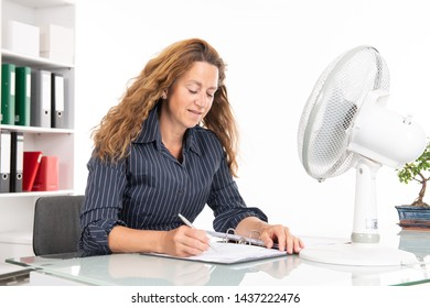 business woman with ventilator at his desk in summerly hot office