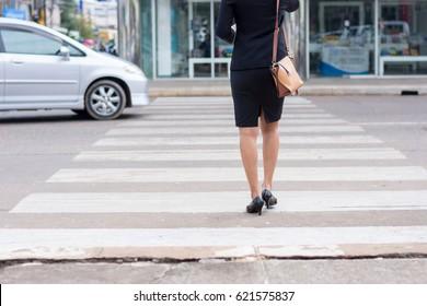 Business woman walking across the crosswalk