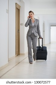 Business woman walking with bag on wheels and talking mobile phone