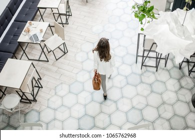 Business woman walking on the tiled floor in the modern cafe, view from above