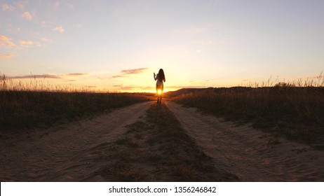 A business woman walks along a country road with a tablet in her hand, the sun miertsaet between women's legs. sexy business woman girl running in the countryside. sexy girl travels in countryside