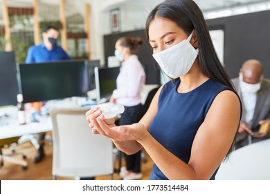 Business woman wearing face mask in the office disinfecting hands because of Covid-19 and corona virus
