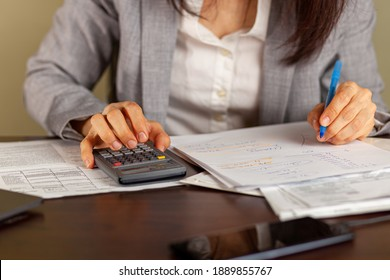 A business woman wearing formal dress is working at an office setting. She is calculating income and expenses using statements, pay slips, receipts. She uses a marker to tick items. Tax return concept