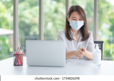 Business woman wearing mask and using personal sanitizer to cleaning her hand in office to keep hygiene.Preventive during the period of epidemic from coronavirus or covid19.