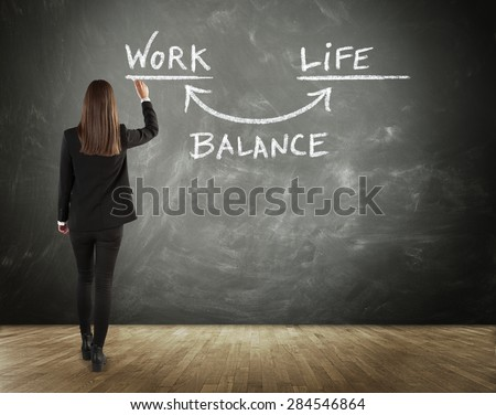 Business woman wearing office black outfit while standing and writing on a chalkboard the plan of keeping the balance between work and life, or between career and family, rear view