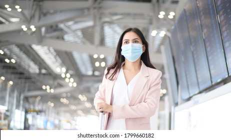 A business woman is wearing protective mask in International airport, travel under Covid-19 pandemic, safety travels, social distancing protocol, New normal travel concept.