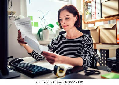 Business woman wearing striped shirt sitting by the window at the desk and reading mail in the office
