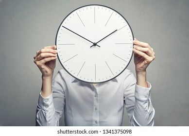 business woman in white blouse covering her face with clock