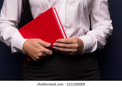 Business woman in white blouse holding red notebook. Isolated on dark background. Hands with red notebook. Close up shot.