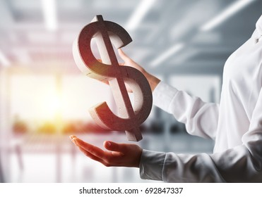 Business woman in white shirt keeping stone dollar sign in hands with office view and sunlight on background. Mixed media.