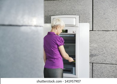 business woman withdrawing cash at bank atm