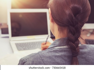 Business woman at work, back side of a woman working on the laptop, working in the office, young successful people concept