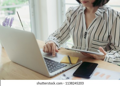 Business, business woman work on the table use computer and tablet with graph chart of marketing analysis job. Business concept
