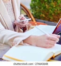 Business woman working in a cafe, writing something in her notebook and using mobile phone