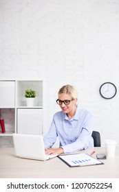 business woman working with computer in office and copy space over white brick wall