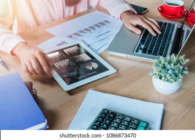 Business woman working with digital tablet and book and document on wooden desk in modern office.