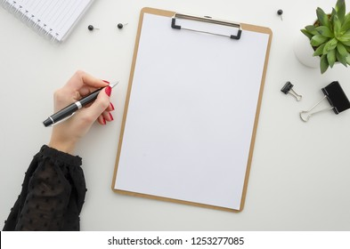 Business woman working with documents. Clipboard mockup template paperwork, financial reports,resume, brief, form, contract. Beautiful female hands in a black blouse with a red manicure holding a pen. - Shutterstock ID 1253277085