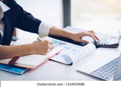 Business woman working with financial data hand using calculator and writing make note with calculate. Business financial and accounting concept.