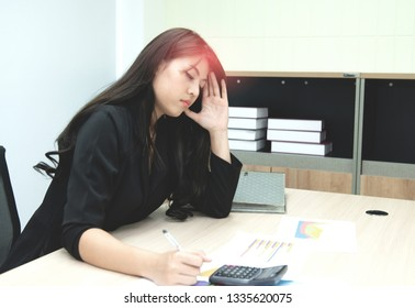 Business woman working and hand holding to the head with headache