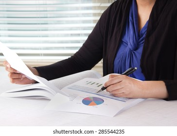 Business woman working in her office room. Person working on financial data in the form of charts. Woman is dress in business casual wear.