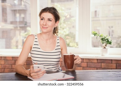 Business woman working at home office. Young woman drinking coffee and typing message on her mobile phone while sitting at her desk.