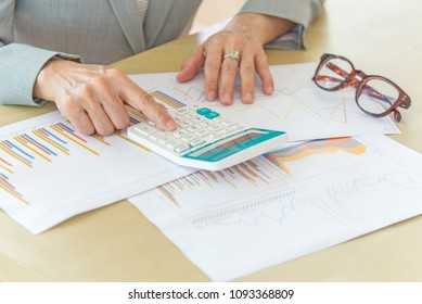 business woman working with laptop, calculator, eyeglasses and report data on wood desk in office.