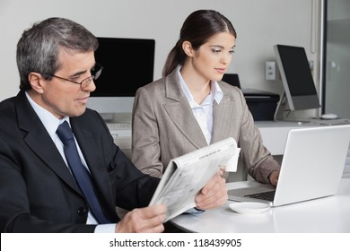 Business woman working with laptop and man reading newspaper in the office