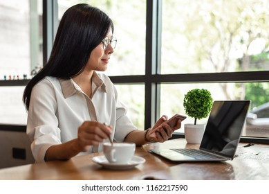 Business woman working with laptop and smartphone and drinking coffee in office. Business and Lifestyles concept. Entrepreneur and Freelance theme. Selective focus on coffee cup