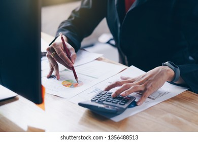 Business woman working with new startup project discussion and analysis data financial report. Using a calculator to calculate numbers.Business financial concept.