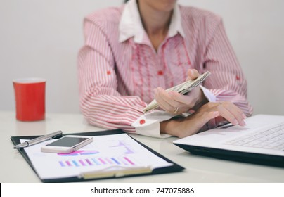 Business woman working. Notebooks, documents, files, a cup and money are  on the table.