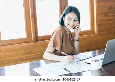 Business woman working in office with documents and use smart phone