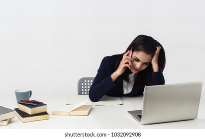 The business woman is working at office hour ,plenty of paper work and books stacked on table,she is using mobile phone and looking at laptop for check the data,busy work.