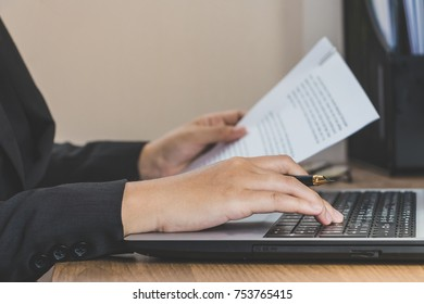 Business woman working at office with laptop and documents on her desk, reading and typing, business concept