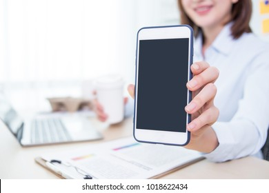 Business woman working at office and showing smart phone