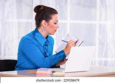 Business woman working in the office at the table.young business woman reading sitting at the desk on office background.Portrait of businesswoman with laptop writes on a document at her office