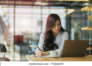 Business woman is working on a computer and writing in notepad in the office.